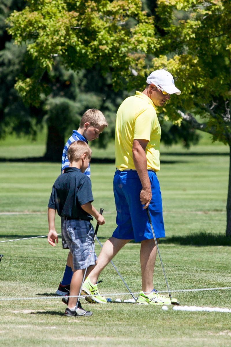 Two young boys walk on the course at The Fox Hill Club with their golf instructor