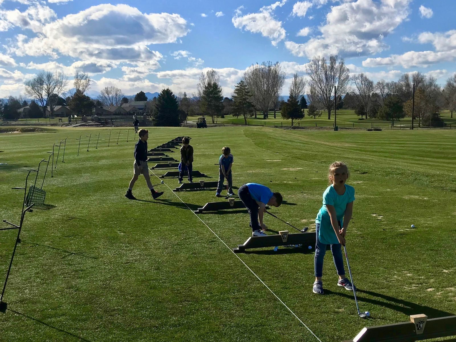 A group of junior golfers practice on the driving range at The Fox Hill Club